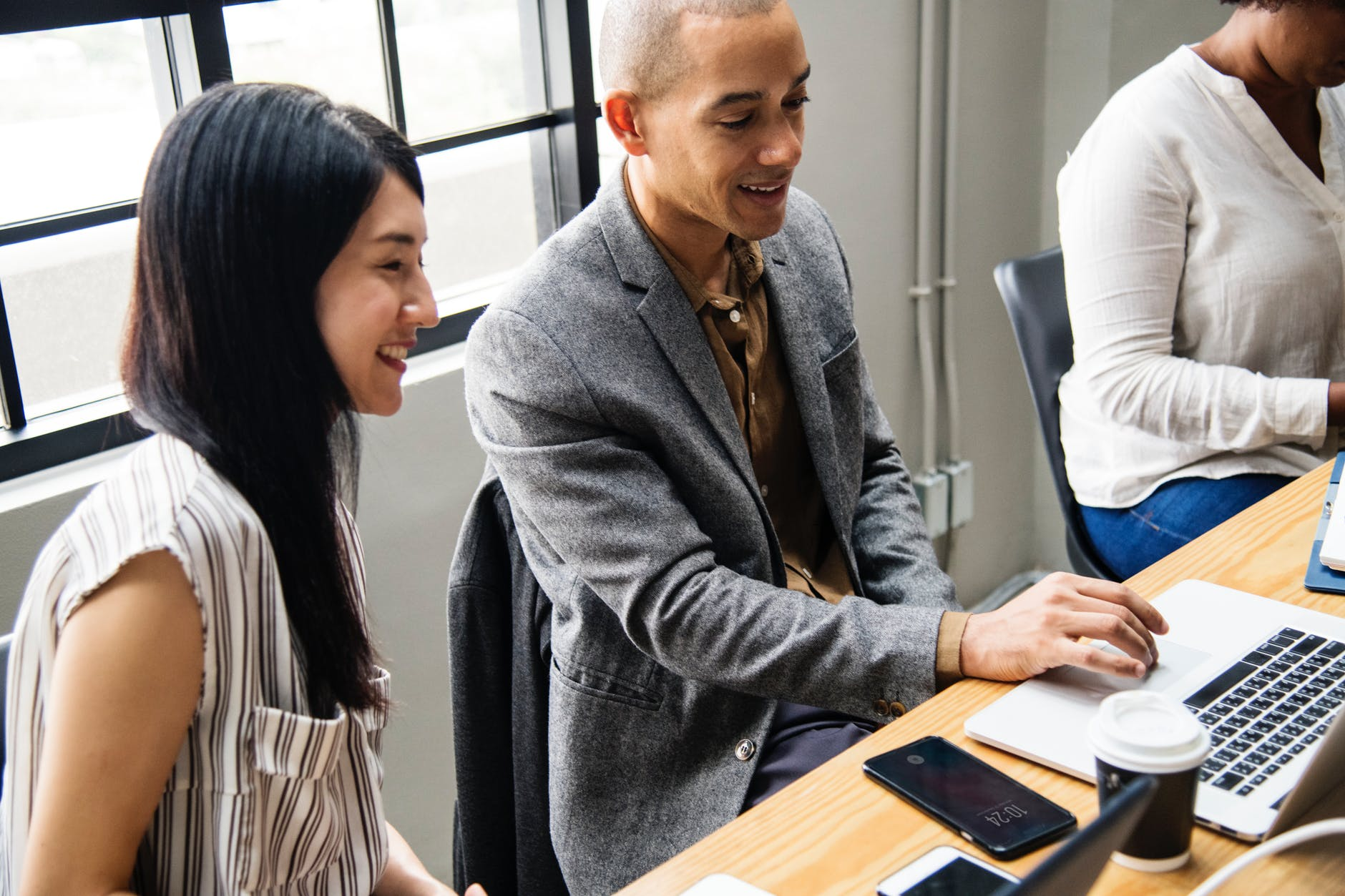 photo of man and woman looking at laptop