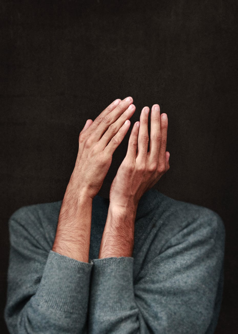 person in gray sweater cover face
