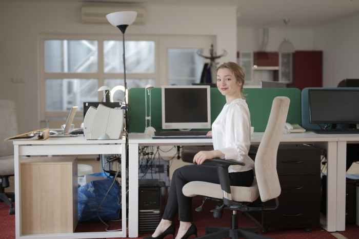 elegant female employee sitting on chair in modern workplace